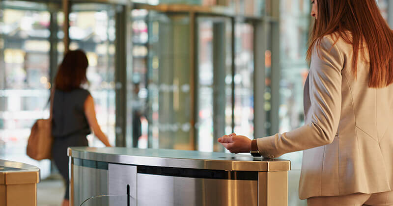 Corporate entry gates with woman using smart watch