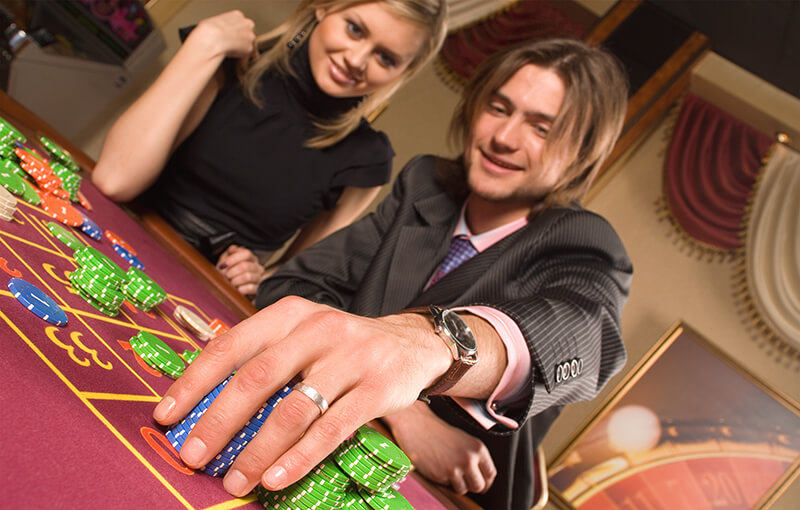 Happy Couple Laying a Bet in a Casino